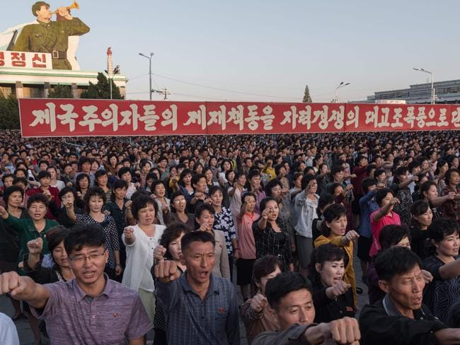 Participants of a mass rally shout slogans as they gather before a banner reading 'let us beat down the sanctions of the imperialists with great progress of self-reliance' on Kim Il-Sung square in Pyongyang. Picture: AFP