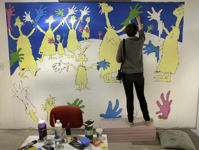 "Cortney Thibodeau, a senior at University of Massachusetts at Amherst, paints a mural based on artwork from the Dr. Seuss book ""Oh, The Thinks You Can Think!"". Picture: AP/Steven Senne"