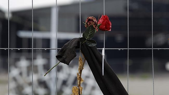 Remembrance ... a rose is fixed to a fence in front of crosses near the site where 21 people died.