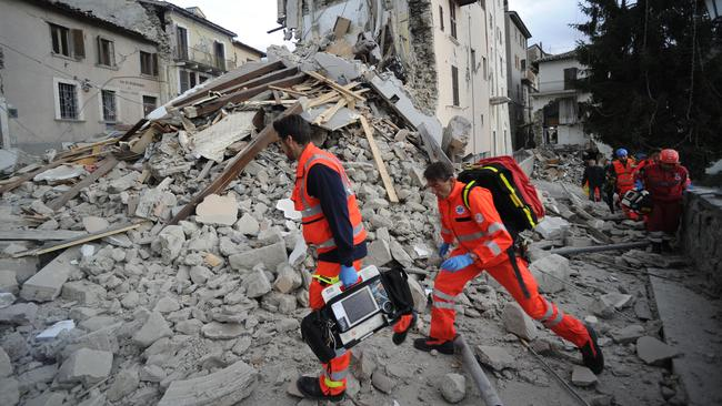 Rescuers search a crumbled building in Arcuata del Tronto, central Italy, where a 6.1 earthquake struck. Picture: AP /Sandro Perozzi.