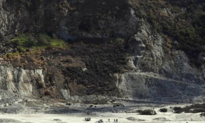 Rescuers stand on the site where three people reportedly died when they fell into a crater in a steamy volcanic field in Pozzuoli, near Naples, Italy. Picture: APSource:AP