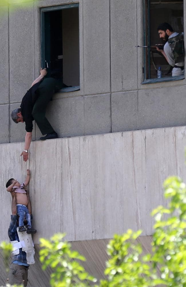 Iranian policemen evacuate a child from the parliament building in Tehran. Picture: AFP