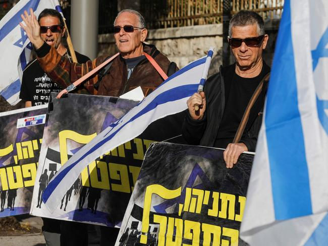 "Israeli protesters wave national flags and hold signs reading in Hebrew ""Netanyahu resign"" during a demonstration in front of Prime Minister Benjamin Netanyahu's residence in Jerusalem. Picture: AFP"