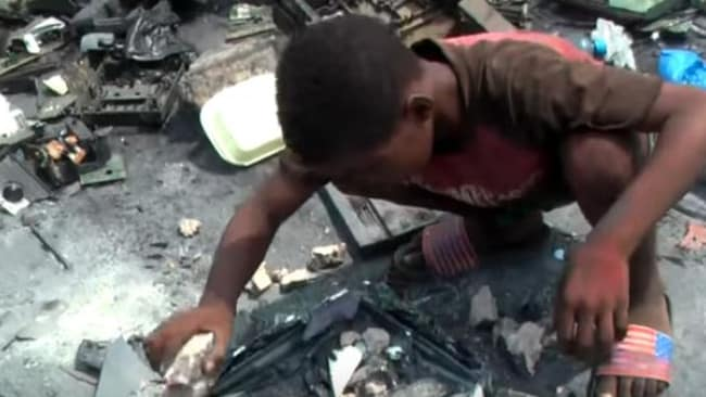 An African child smashes computer parts for money at Agbogbloshie, the world's biggest computer dump where Australian e-waste has been located. Picture: Radio National.