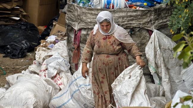 A woman looks for recyclable items in a waste dump outside Incirlik Air Base, Turkey, Friday, Aug. 30, 2013. U.N. Secretary-General Ban Ki-moon said the Inspection team in Syria is expected to complete its work Friday and report to him Saturday. (AP Photo/Vadim Ghirda)