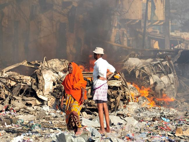 A man and woman look at the damages on the site of the explosion of a truck bomb in the centre of Mogadishu. Picture: AFP