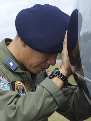 An Indonesian Navy airman prays on his plane before searching the waters near Bangka Island. Picture: Ed Wray