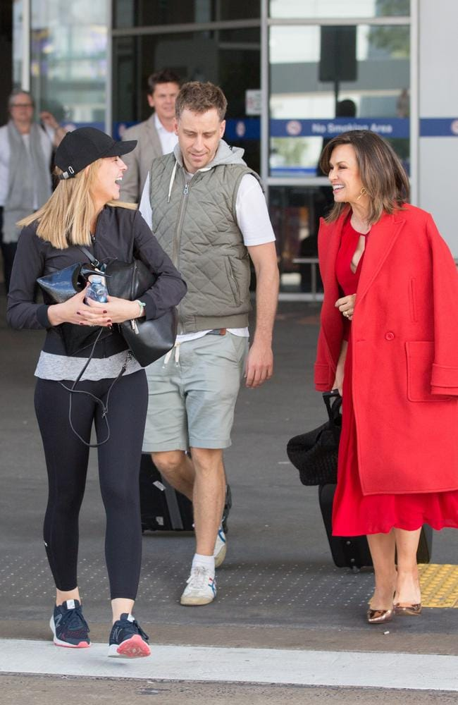 Lisa Wilkinson and Carrie Bickmore with her partner Chris Walker outside Melbourne airport in December. Picture: Mega
