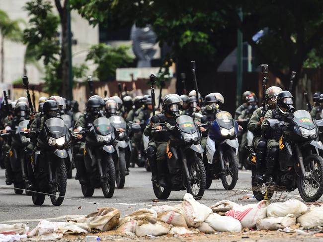 National Guard motorcyclists in riot gear charge on opposition activists blocking an avenue in Caracas. Picture: AFP