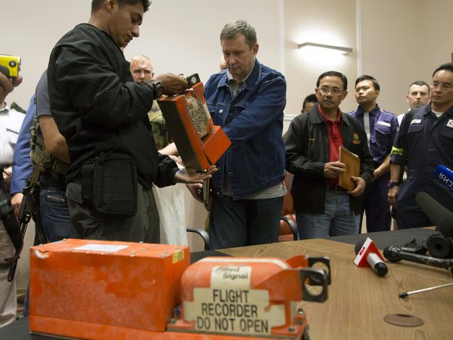 What the world was waiting for ... a Malaysian investigator, left, takes a black box from Malaysia Airlines Flight 17 as it is handed over by a Donetsk People's Republic official. Picture: Dmitry Lovetsky