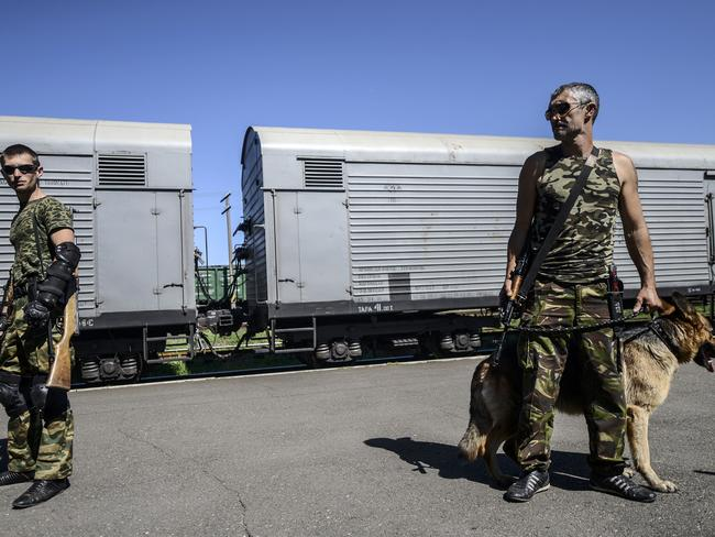 Armed pro-Russian separatists stand guard in front of wagons containing the remains of victims from the downed Malaysia Airlines Flight MH17, at a railway station in the eastern Ukrainian town of Torez. Picture: AFP