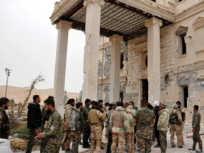 Ruins ... Syrian government soldiers gather outside a damaged palace, in Palmyra, central Syria. Picture: SANA via AP