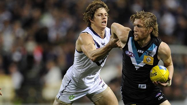 Port Adelaide midfielder Aaron Young brushes off Fremantle star Nat Fyfe. Picture: PerthN
