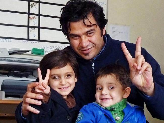 Shocking attack ... reporter Sardar Ahmad poses with daughter Nilofar (left) and son Omar (right) at the AFP office in Kabul in 2012. Ahmad, his wife, and the two children pictured were gunned down when four men attacked the Serena hotel where they were celebrating Persian new year. Picture: Joris Fioriti