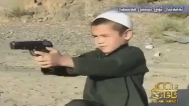 A young boy aims a pistol at a target as he undergoes terrorist training to be Jihadi warrior. Picture: Youtube