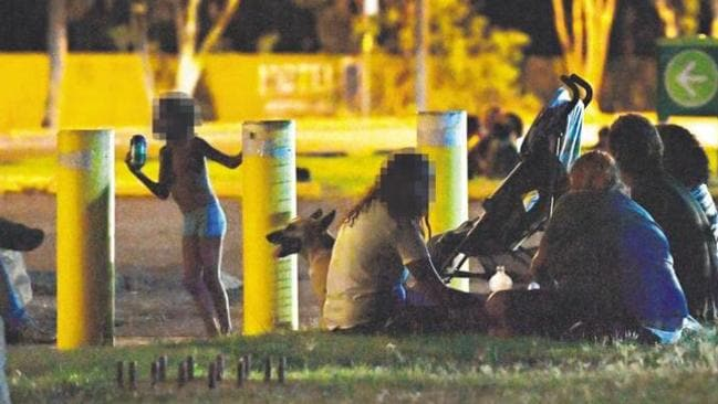 A family with young children sit beside the road near the BP service station in Tennant Creek after 10pm.