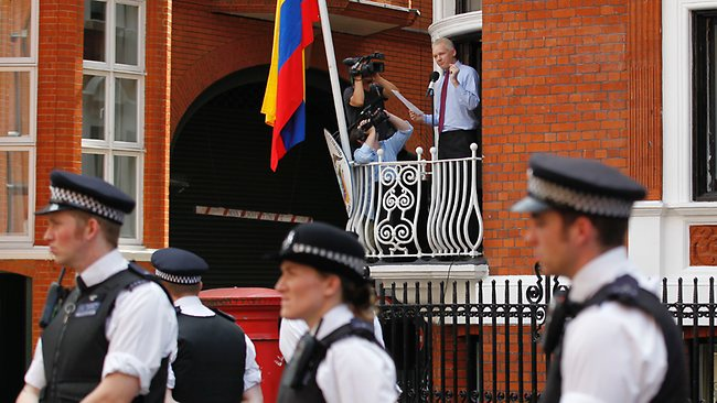 Surrounded by British police officers, WikiLeaks founder Julian Assange makes a statement to the media and supporters at a window of Ecuadorian Embassy in central London. AP Photo/Sang Tan
