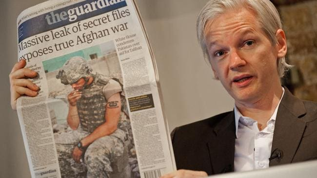 Julian Assange holds up a copy of the Guardian newspaper during a press conference in London.
