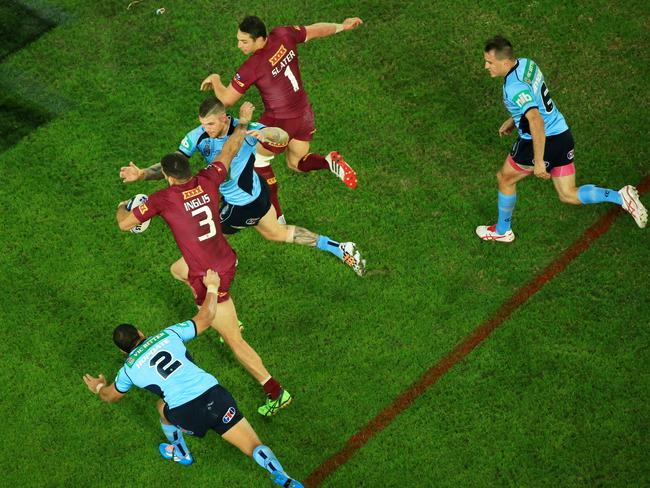 Queensland's Greg Inglis makes a break through the NSW defence during game two of State of Origin at ANZ Stadium.