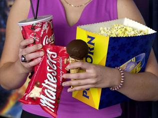 JAN 11, 2001 Moviegoer holding her supplies at Hoyts, /George /St, /City, which cost $18.20 as well as cost of entry ticket. PicBrad/Newman. Food / Drink coca cola packet of maltesers popcorn chocolate top ice cream cone fast foods generic