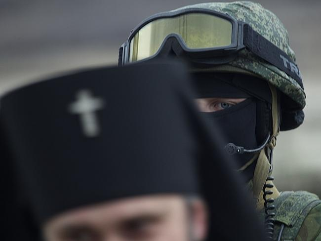 A Russian solder is seen behind Ukrainian Orthodox Archbishop Clement outside a Ukrainian military base in the village of Perevalne.
