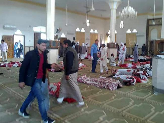 Egyptians walk past bodies following an attack at the Rawda mosque, in the North Sinai which killed hundreds. Picture: AFP