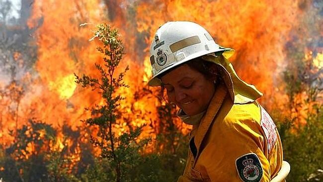 Kerri McGrath turns her head away from the heat as firefighters prepare the grounds of Bell with back-burning operations. Pictur