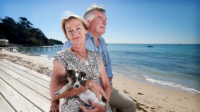 Shane and Catherine McCarthy, parents of former Collingwood and Port Adelaide player John, with their dog Poppy at Shelley Beach near their home at Portsea, Victoria. Picture: Calum Robertson