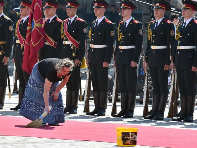 Clean sweep ... a woman sweeps a red carpet in front of soldiers prior to a ceremony for the new Ukrainian President Petro Poroshenko. Picture: Sergei Supinsky
