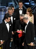 "'La La Land' producer Jordan Horowitz consults with production staffer regarding a presentation error of the ""Best Picture"" award (later awarded to 'Moonlight'), as composers Justin Hurwitz and actor Emma Stone look on onstage during the 89th Annual Academy Awards. Picture: Getty"