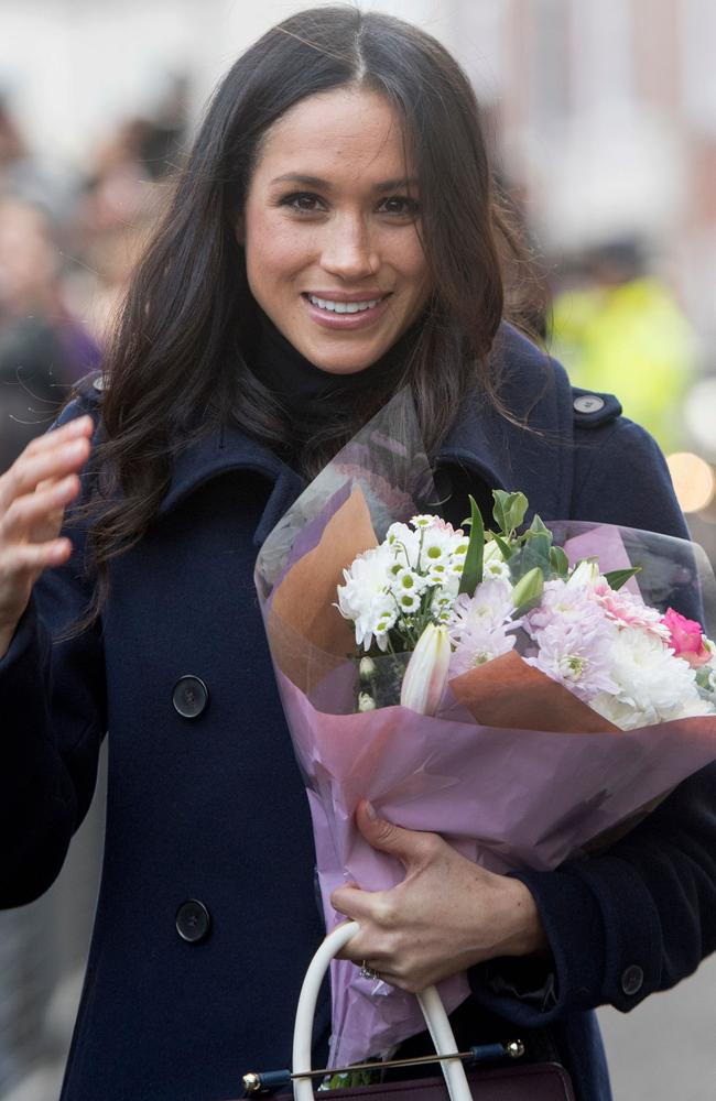 Meghan Markle was handed flowers and greeted by hundreds of fans taking selfies and videos on her first public appearance since becoming engaged. Picture: AP PHOTO / POOL AND AFP PHOTO / JEREMY SELWYN