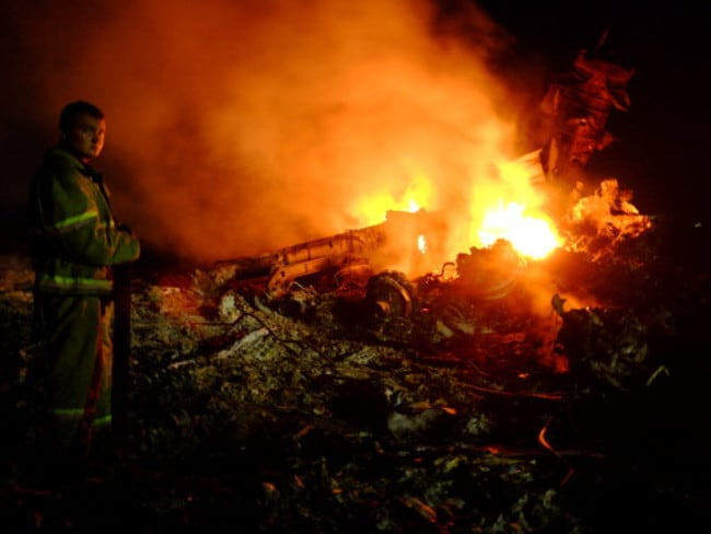 Up in flames ... a firefighter stands as flames burst among the wreckage of the Malaysian airliner.