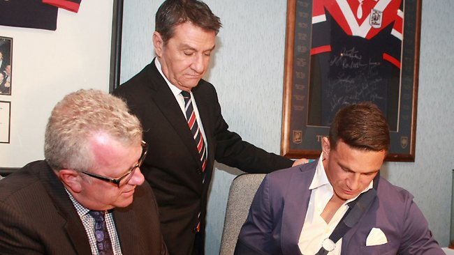 Nick Politis (centre) watches as Sonny Bill Williams (R) signs his Roosters contract.