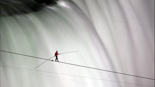 Acrobat Nik Wallenda midway through his 1800-foot tightrope walk across Niagara Falls, the first time the feat has been attempted at that spot at the falls.