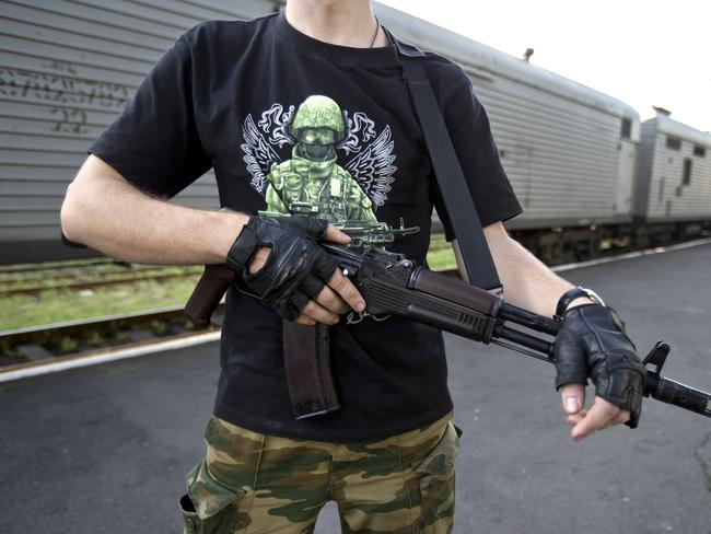 Site security ... An armed pro-Russian rebel, wearing a T-shirt that depicts a Russian soldier during the Crimea annexation, secures the area next to a refrigerated train loaded with the bodies of victims, in Torez, eastern Ukraine.