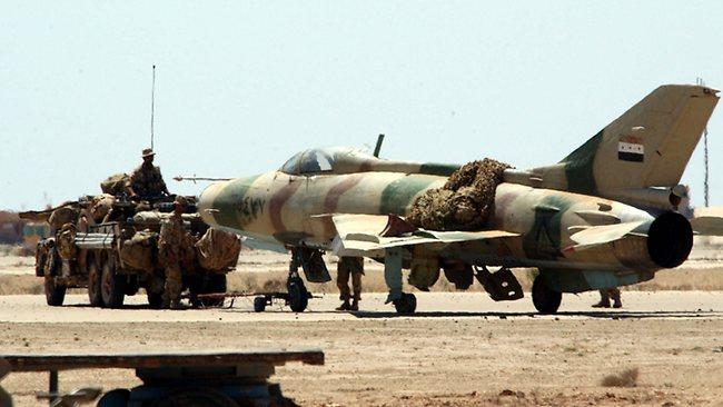 An SAS Long Range Patrol Vehicle tows a Russian built Iraqi air force Mig jet fighter at al Asad air base.