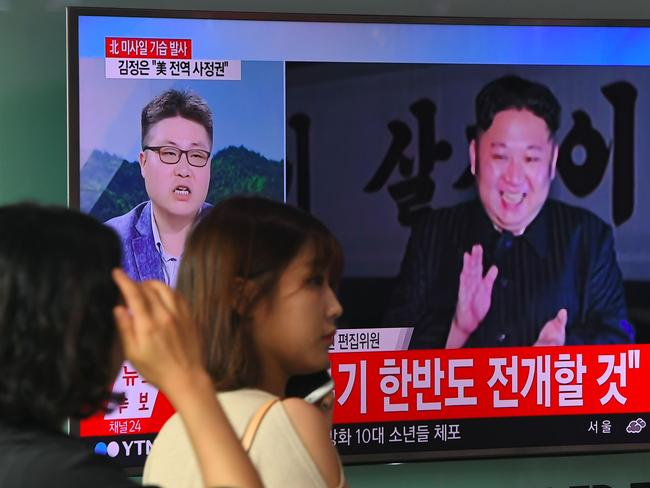 A woman walks past a television screen showing a video footage of North Korean leader Kim Jong-un celebrating his country's latest test launch of an intercontinental ballistic missile (ICBM). Picture: AFP