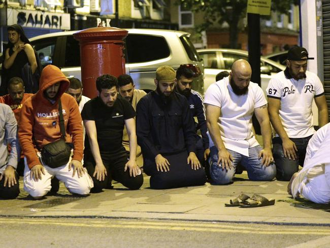 Local people observe prayers at Finsbury Park, where a vehicle struck pedestrians. Picture: AP