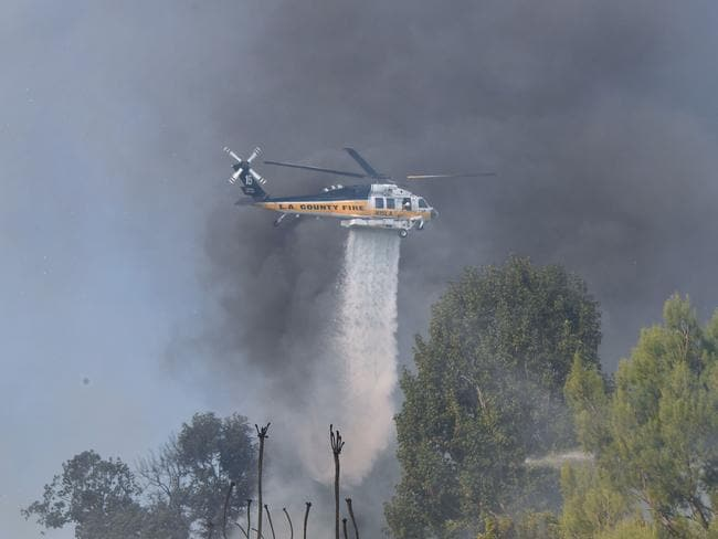 A helicopter flies over Bel Air. Celebrities have taken to social media to voice their concern over California's bushfires. Picture: AFP/Frederic J Brown