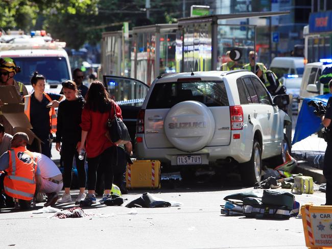 Police, fire and paramedics treat a number of pedestrians on the corner of Flinders and Elizabeth streets in Melbourne after a car ploughed through the busy intersection. Picture: Aaron Francis/The Australian
