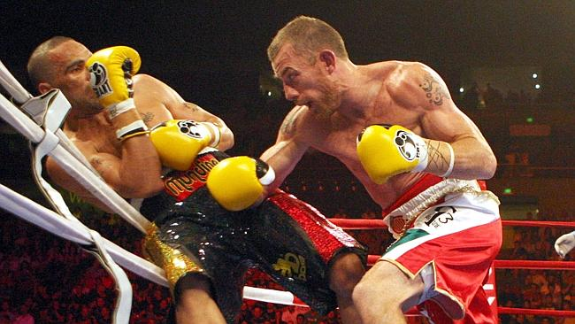 Anthony Mundine is forced on to the ropes by Garth Wood, who sprung a huge upset in their 2010 fight.