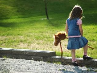 RendezView. Little girl lonely in the yard holding her toy horse. (Pic: iStock)