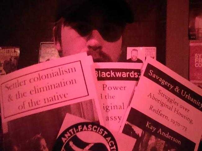 Shayne showing off some of the Antifa propaganda the group uses to recruit members.