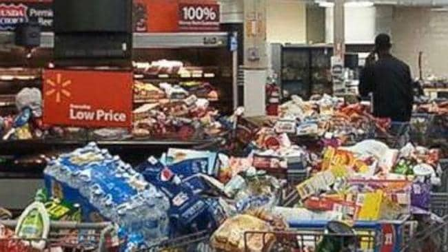 Too late ... The trolleys overwhelmed with food left when the card limit was reimposed at Walmart in Springhill, Louisiana. Picture: YouTube