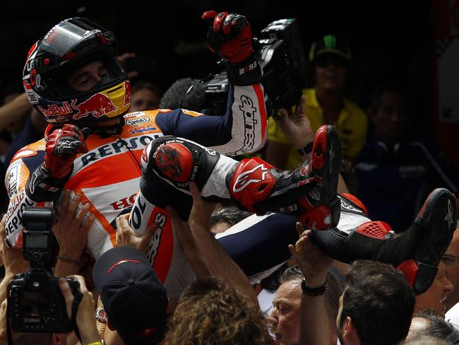 Honda celebrate by hoisting Marquez aloft.