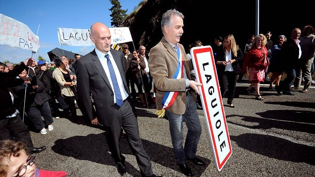 Mayor Vincent Alazard, centre, flanked by French lawyer and MP deputy of Aveyron, Stephane Mazars, removing a road sign reading the name of the village Laguiole. Picture: AFP