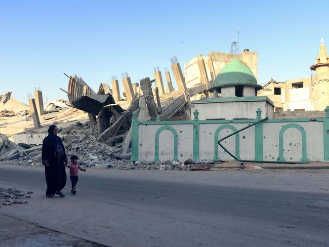 A woman and child walk past the destroyed Omari mosque.