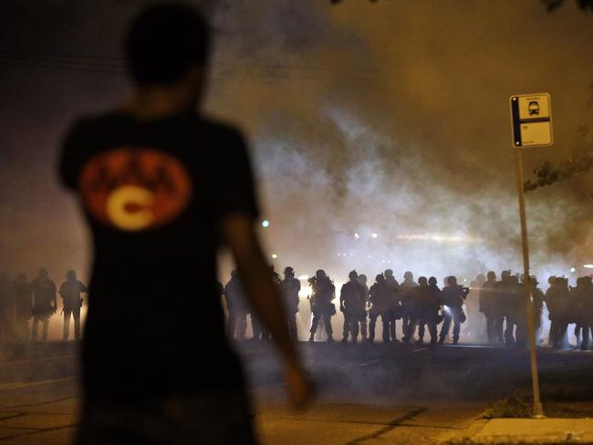 Heavy blue line ... A man watches as police, some armed with assault rifles, walk through a cloud of smoke during a clash with protesters in Ferguson, Missouri. Source: AP