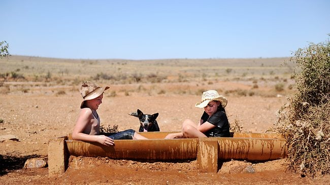 Drea Galloway and his sister Gracie cool off in a water trough from the 45 degree heat at Mt Gipps Station, Broken Hill, Western NSW. Picture: Braden Fastier