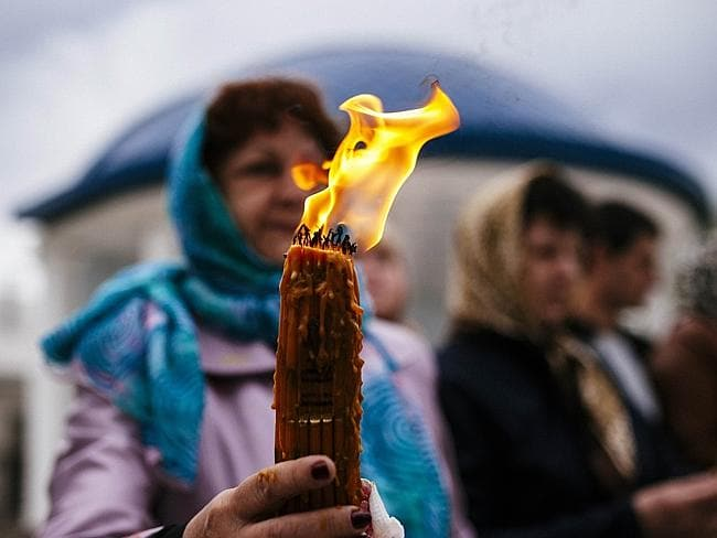 Prayers for peace ... Orthodox Christians hold candles as they take part in Easter celebr